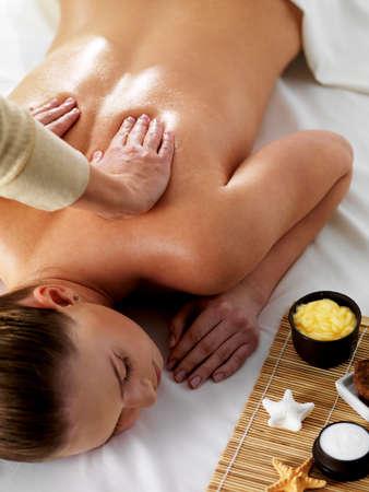 massaggio: Relax e gioia nel massaggio per la giovane donna bella nel salone di bellezza spa - verticale