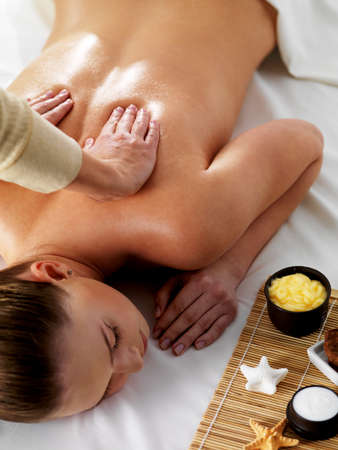 massage: Relaxation and joy in massage for young beautiful woman in spa beauty salon - vertical