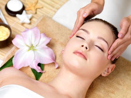 massaggio: Beautiful young woman avendo massaggio termale della testa nel salone di bellezza - al chiuso