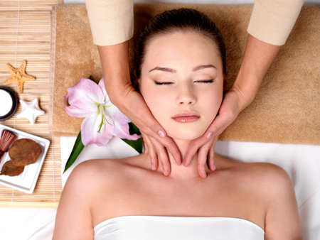 Beautiful young girl getting massage for neck in spa salon - indoors photo