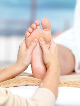 feet relaxing: Massage on the foot in spa salon, close-up shot - colored background