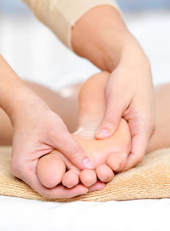 massage: Healthy massage for caucasian foot in spa beauty salon - close-up Stock Photo