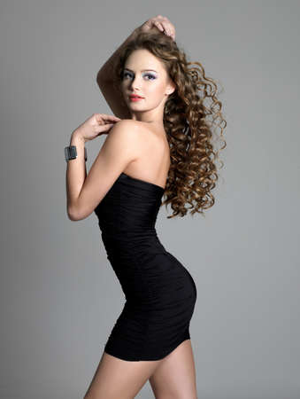 Elegance and beauty of pretty woman in fashion black dress - greay background photo