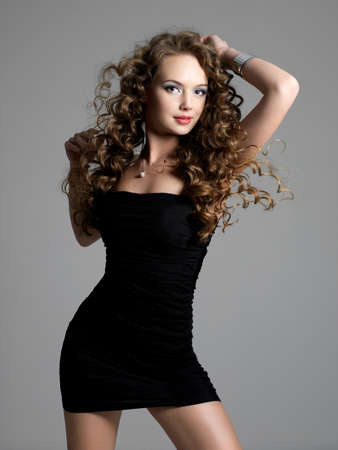 Portrait of beautiful glamour elegance woman with long curly hair posing at studio photo