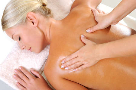 body massage: Young woman taking a massage for her body in beauty salon