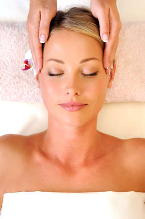 Massage on the face for young woman in beauty salon photo