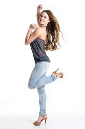 Happy and joy beautiful girl in fashion stylish jeans - isolated on white.  Fashion model posing at studio photo