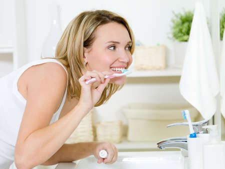 bathroom women: Woman cleaning teeth with toothbrush in bathroom, profile portrait Stock Photo