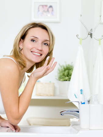 face cream: Beautiful young woman applying cosmetic cream on face standing in the bathroom Stock Photo