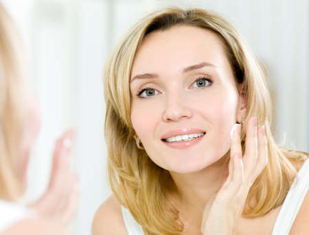 woman face cream: Beautiful young woman applying cosmetic cream on face standing in the bathroom Stock Photo