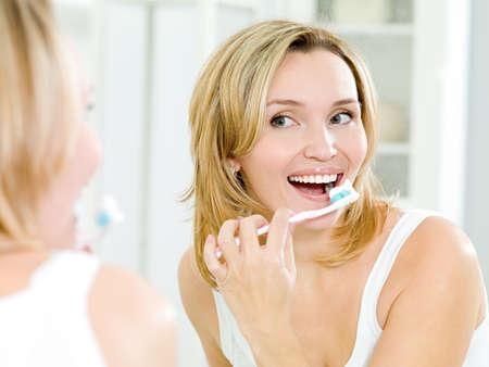 mujer limpiando: Joven sonriente limpieza de dientes con cepillo de ba�o