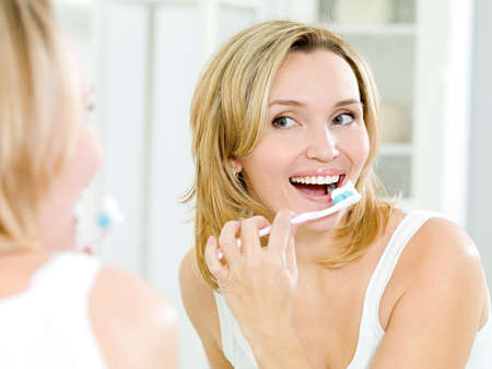 Young smiling woman cleaning teeth with toothbrush in bathroom photo