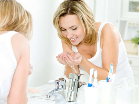 Young happy woman washing face with water standing in bathroom Stock Photo - 10668389