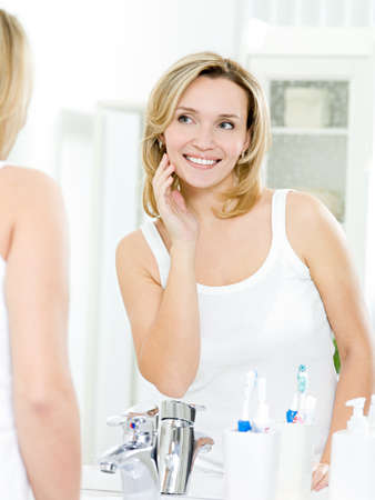 Beautiful smiling young woman with fresh skin of face posing in bathroom Stock Photo