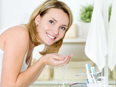 washing face: Young happy woman washing face with water standing in bathroom