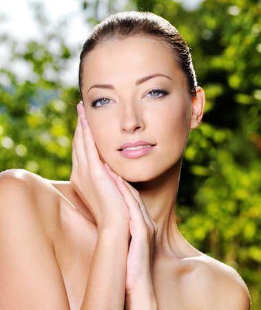 Beautiful sexy face of an young woman with fresh health skin. Female posing on the nature. Model stroking her body. Stock Photo - 10668406