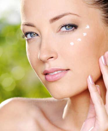 Beautiful sexy woman applying cosmetic cream on skin near eyes - Outdoors Imagens