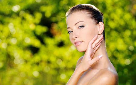 Mooie sexy gezicht van een jonge vrouw met verse gezondheid van de huid. Vrouw die zich op de natuur. Model streelde haar lichaam. Stockfoto