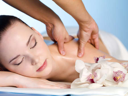 Young woman in spa salon having massage of  shoulder - horizontal