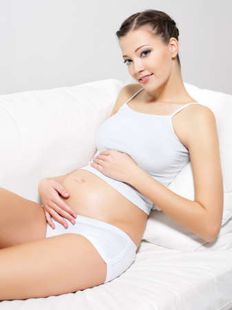 Young beautiful pregnant woman sitting on sofa and touching her belly and looking at camera photo