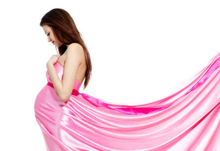 Youn beautiful pregnant woman in rosy dress - white background photo