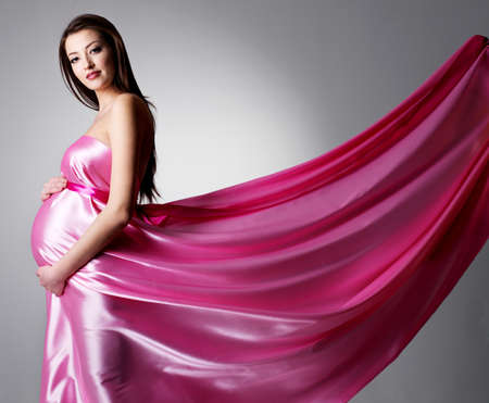 Beauty of young pregnant woman in beautiful pink dress- grey background photo
