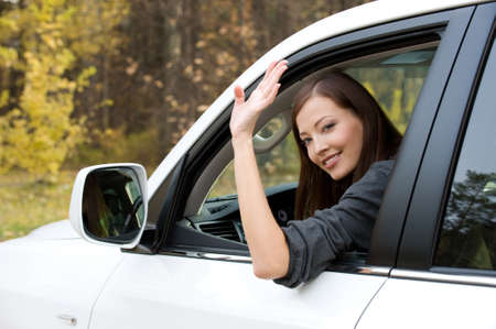 Successful beautiful young woman in the new car  - outdoors photo