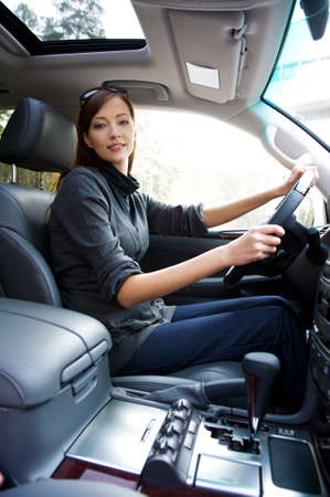 car inside: beautiful young happy woman posing inside of  the new car