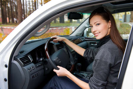 sexy woman car: Young smiling  beautiful woman sits in the new car  - outdoors Stock Photo