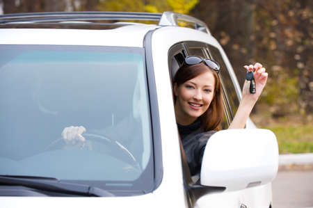 car key: Happy successful woman with keys from the new car - outdoors  Stock Photo