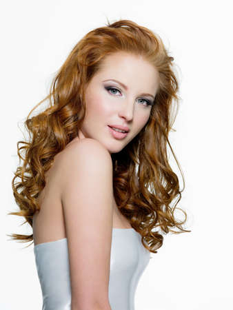 Beautiful young red-haired woman with long beauty curly-headed hairs - isolated on white