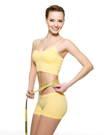shaping: Pretty smiling woman measuring waist with  measurement type isolated on white