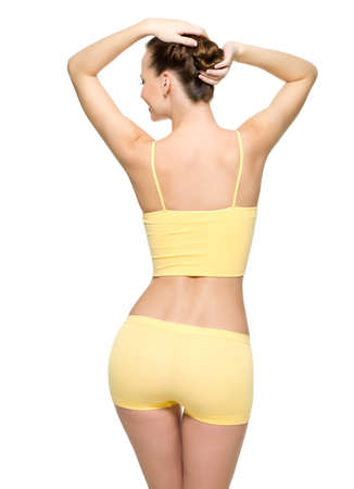 Back view of a perfect female body with thin waist posing isolated on white background photo