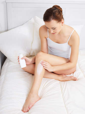 Pretty young adult woman applying cream for skin on legs - indoors photo
