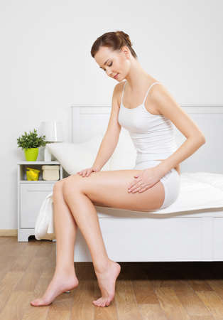 Beautiful woman touching her smooth health hip sitting on bed