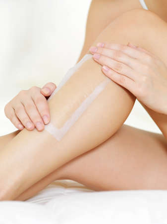 depilation  of female legs by wax - close-up shot photo