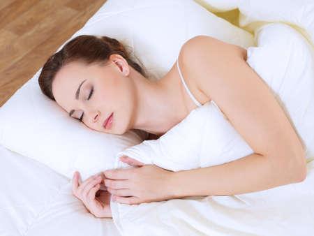 ハイアングルビュー: 寝室のベッドで眠っている女性のハイアングル 写真素材