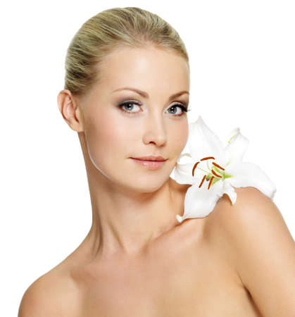Beautiful young woman with fresh clean skin and white flower on shoulder - isolated photo