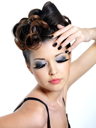 ringlet: Glamour woman with  fashion eye make-up   and black nails near the face Stock Photo