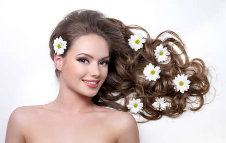 Smiling woman with beautiful long hair wna flowers in it - white background photo