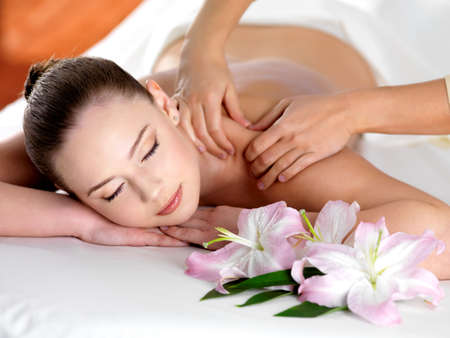 pampering: Spa massage on a shoulder for young beautiful woman in  beauty salon - indoors Stock Photo