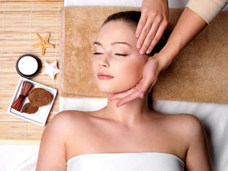 the neck: Coccole e massaggi per il bel volto della giovane donna in salone spa - interni Archivio Fotografico