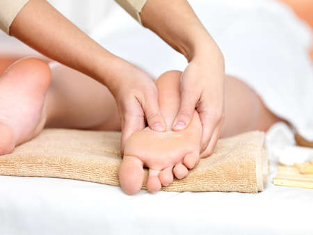 feet relaxing: Relaxing massage on the foot  in spa salon - indoors