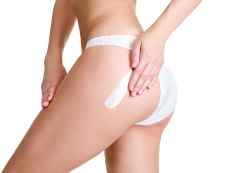 cellulite: Female applying cosmetic cream from cellulite on leg - isolated onwhite Stock Photo