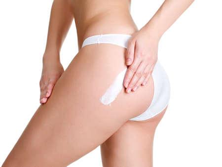 mujer celulitis: Mujer aplicar crema cosm�tica de la celulitis en la pierna - onwhite aislados
