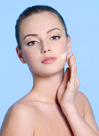 Portrait of young woman applying cream on her beautiful fresh face - blue background photo