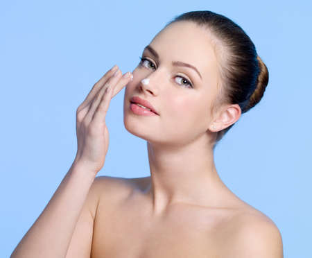woman face cream: Beautiful sexy young girl applying cream on her nose - blue background