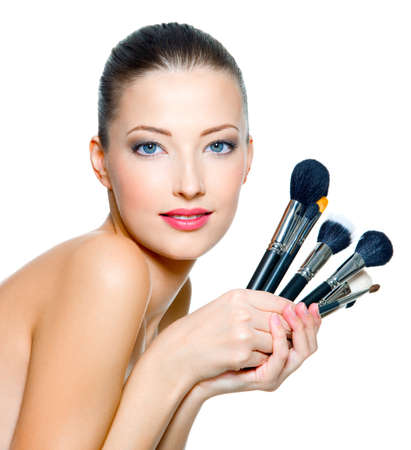 makeup a brush: Portrait of the beautiful woman with make-up brushes near attractive face. Adult girll posing over white background