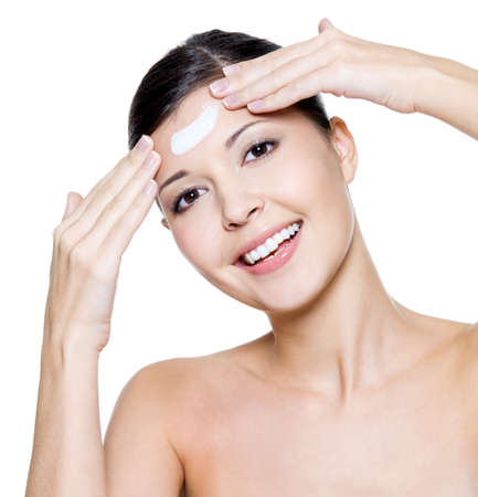 Beautiful young happy woman applying cosmetic cream on forehead. Isolated on white background Stock Photo - 11172503