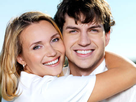 portrait of young happy beautiful couple on blue skiy background photo
